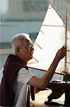 mature man working on model sail boat and smiling Stock Photo - Premium Royalty-Free, Artist: IIC, Code: 656-03519503