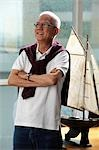 mature man folding his arms and smiling in front of model sail boat Stock Photo - Premium Royalty-Free, Artist: IIC, Code: 656-03519530