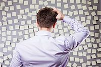 Businessman Looking at a Wall Full of Self Adhesive Notes Stock Photo - Premium Royalty-Freenull, Code: 600-03520293