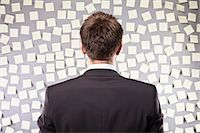 Businessman Looking at a Wall Full of Self Adhesive Notes Stock Photo - Premium Royalty-Freenull, Code: 600-03520294