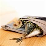 Two mackerel in a fabric napkin with mushroom and thyme Stock Photo - Premium Royalty-Free, Artist: Westend61, Code: 659-03523746