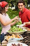 Young woman serving green salad at a barbecue Stock Photo - Premium Royalty-Free, Artist: Kevin Dodge, Code: 659-03524299
