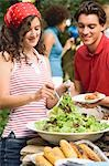 Young woman serving green salad at a barbecue Stock Photo - Premium Royalty-Free, Artist: Kevin Dodge, Code: 659-03524300