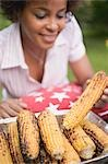 Woman taking grilled corn on the cob out of aluminium dish Stock Photo - Premium Royalty-Free, Artist: Kevin Dodge, Code: 659-03524336