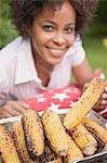 Woman taking grilled corn on the cob out of aluminium dish Stock Photo - Premium Royalty-Free, Artist: Kevin Dodge, Code: 659-03524337