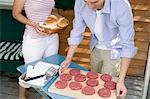 Man preparing burgers for grilling, woman bringing buns Stock Photo - Premium Royalty-Free, Artist: Kevin Dodge, Code: 659-03524552