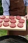 Man holding raw burgers on chopping board over barbecue Stock Photo - Premium Royalty-Free, Artist: Kevin Dodge, Code: 659-03524553