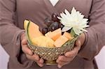 Woman holding bowl of fresh fruit with water lily Stock Photo - Premium Royalty-Free, Artist: Glowimages, Code: 659-03524623