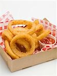 Deep-fried onion rings with ketchup in a cardboard box Stock Photo - Premium Royalty-Free, Artist: ableimages, Code: 659-03529168