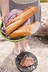 Woman with baguettes at a barbecue on a river bank Stock Photo - Premium Royalty-Free, Artist: Kevin Dodge, Code: 659-03529496