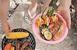 Woman holding plate of grilled food at barbecue on river bank Stock Photo - Premium Royalty-Free, Artist: Kevin Dodge, Code: 659-03529509