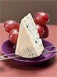 Piece of blue cheese on cheese knife, red grapes behind Stock Photo - Premium Royalty-Freenull, Code: 659-03530745