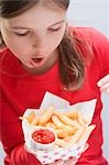 Girl holding chips with ketchup Stock Photo - Premium Royalty-Free, Artist: ableimages, Code: 659-03531215