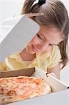 Girl looking at fresh pizza in pizza box Stock Photo - Premium Royalty-Freenull, Code: 659-03531230