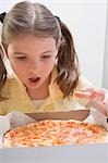Girl looking in wonder at fresh pizza in box, Stock Photo - Premium Royalty-Freenull, Code: 659-03531231