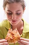 Young woman with partly eaten slice of pizza Margherita Stock Photo - Premium Royalty-Freenull, Code: 659-03531250