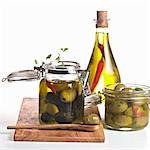 Pickled olives in jars and a bottle of chilli oil Stock Photo - Premium Royalty-Freenull, Code: 659-03533882