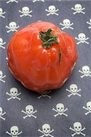 poison - Tomato on a patterned background (skulls and crossbones) Stock Photo - Premium Royalty-Freenull, Code: 659-03535616