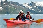 Pair of kayakers pause to take a photo as they paddle through Aialik Bay at Kenai Fjords National Park. Summer on the Kenai Peninsula Stock Photo - Premium Rights-Managed, Artist: AlaskaStock, Code: 854-03538078