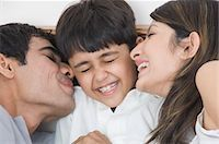 preteen kissing - Couple smiling with their son Stock Photo - Premium Rights-Managednull, Code: 857-03553779