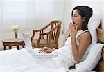Woman using a laptop on the bed, Gurgaon, Haryana, India
