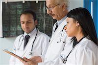 Three doctors examining a report, Gurgaon, Haryana, India Stock Photo - Premium Rights-Managednull, Code: 857-03554226