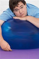 fat man balls - Overweight Man Resting on Exercise Ball, portrait Stock Photo - Premium Royalty-Freenull, Code: 693-03557449
