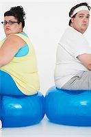 fat man balls - Unhappy overweight man and woman sitting back to back on exercise balls, portrait Stock Photo - Premium Royalty-Freenull, Code: 693-03557462