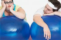 fat man balls - Disinterested overweight man and woman lying on Exercise Balls, close up Stock Photo - Premium Royalty-Freenull, Code: 693-03557463
