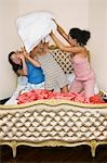 Teenage Girls pillow fighting, kneeling on funky bed