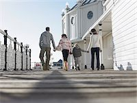 Family holding hands, walking along pier, back view, low angle view Stock Photo - Premium Royalty-Freenull, Code: 693-03557761