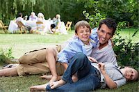 Father and two sons (7-10) having fun on grass in garden Stock Photo - Premium Royalty-Freenull, Code: 693-03565220