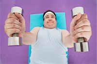 fat man exercising - Overweight Man lying down Lifting dumbbells, overhead view Stock Photo - Premium Royalty-Freenull, Code: 693-03565331