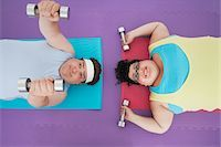 fat man exercising - Overweight man and woman lying down lifting dumbbells, overhead view Stock Photo - Premium Royalty-Freenull, Code: 693-03565334