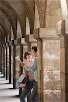 Couple with shopping bags looking at map under archway Stock Photo - Premium Royalty-Freenull, Code: 693-03565474