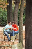 Couple reading guide book, sitting on chairs, in park Stock Photo - Premium Royalty-Freenull, Code: 693-03565482