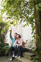 Couple sitting on steps looking up Stock Photo - Premium Royalty-Freenull, Code: 693-03565487