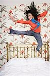 Teenage Girl, arms outspread, kicking, jumping on bed