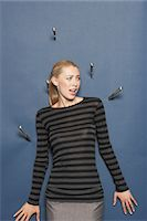 people in panic - Woman surrounded by thrown knives against blue background Stock Photo - Premium Royalty-Freenull, Code: 693-03565594