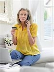 Woman holding credit card using phone in living room Stock Photo - Premium Royalty-Free, Artist: Raoul Minsart, Code: 693-03565765