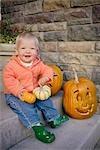 Baby girl sitting on steps by carved pumpkins Stock Photo - Premium Royalty-Free, Artist: Sheltered Images, Code: 621-03568723