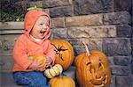 Baby girl sitting on steps by carved pumpkins Stock Photo - Premium Royalty-Free, Artist: Sheltered Images, Code: 621-03568725