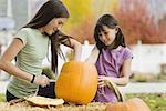 Girls carving pumpkin Stock Photo - Premium Royalty-Free, Artist: Sheltered Images, Code: 621-03569216
