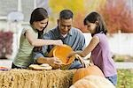 Girls and father carving pumpkins Stock Photo - Premium Royalty-Free, Artist: Sheltered Images, Code: 621-03569218