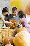 Girls and father carving pumpkins Stock Photo - Premium Royalty-Free, Artist: Sheltered Images, Code: 621-03569219