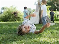Young boy laying in grass with boys at tipi in background Stock Photo - Premium Royalty-Freenull, Code: 618-03571716