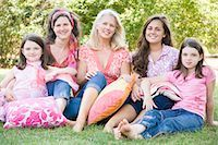 Portrait of two mature women sitting in a park with their daughters and smiling Stock Photo - Premium Royalty-Freenull, Code: 618-03572341