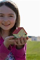 A girl holding a miniature house Stock Photo - Premium Royalty-Free, Artist: ableimages, Code: 653-03575817