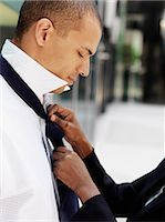 A businesswoman tying her boyfriend's tie Stock Photo - Premium Royalty-Freenull, Code: 653-03576018