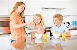 Mother pouring milk for children in kitchen Stock Photo - Premium Royalty-Freenull, Code: 635-03577404